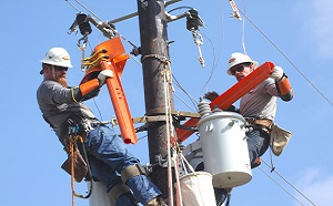 AE Linemen replacing fuses on a utility pole